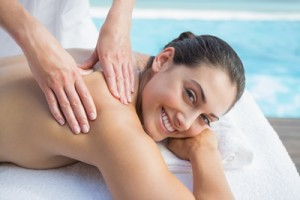 Smiling brunette getting a massage poolside looking at camera outside at the spa