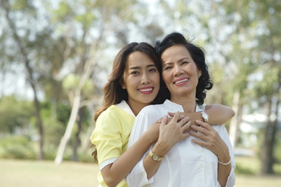 Portrait of beautiful Vietnamese lady hugging her mother from behind